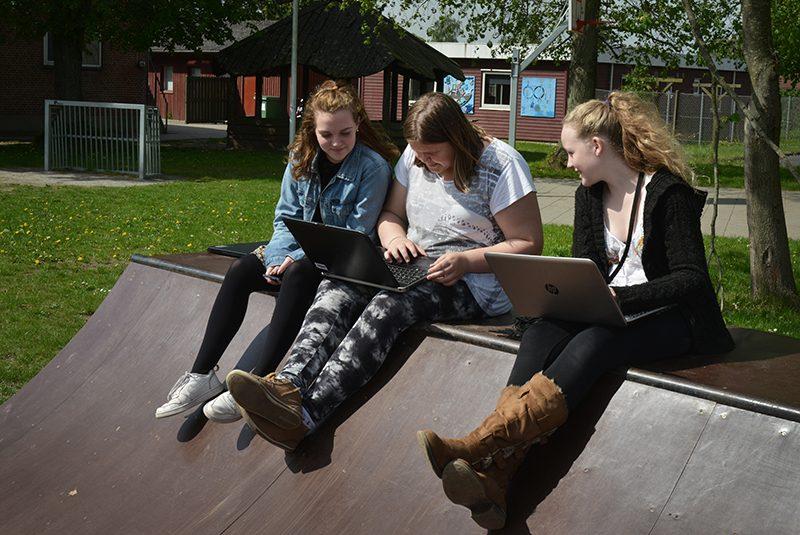 Teenagebørn der sidder og laver skolearbejde på en skaterrampe