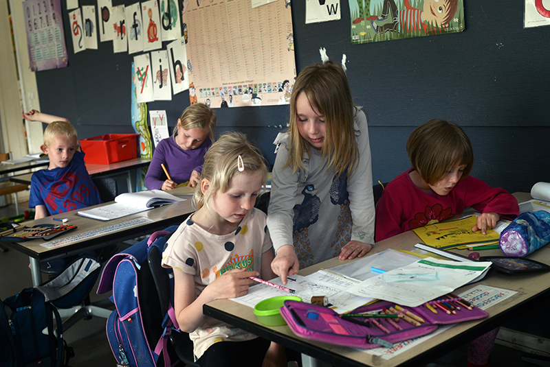Børn laver lektier i klasseværelset