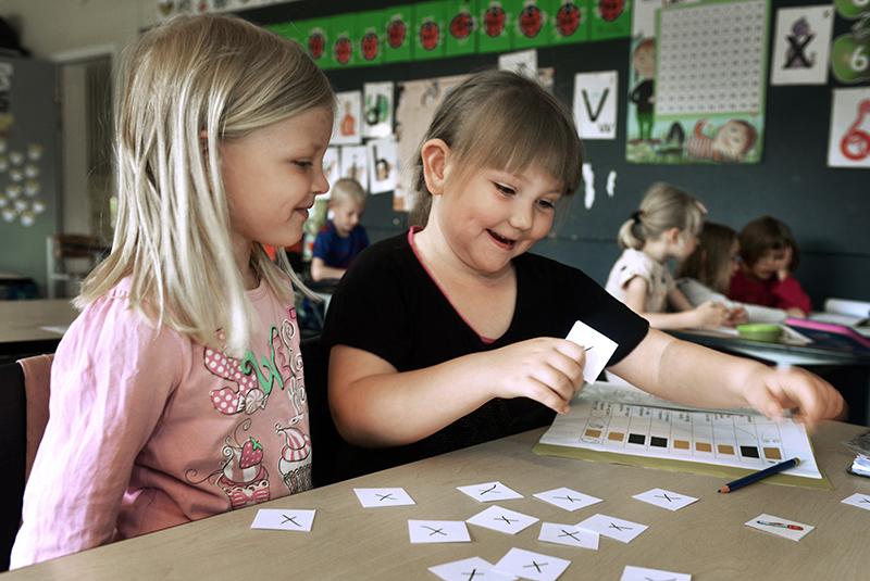 To piger arbejder i klasseværelset.