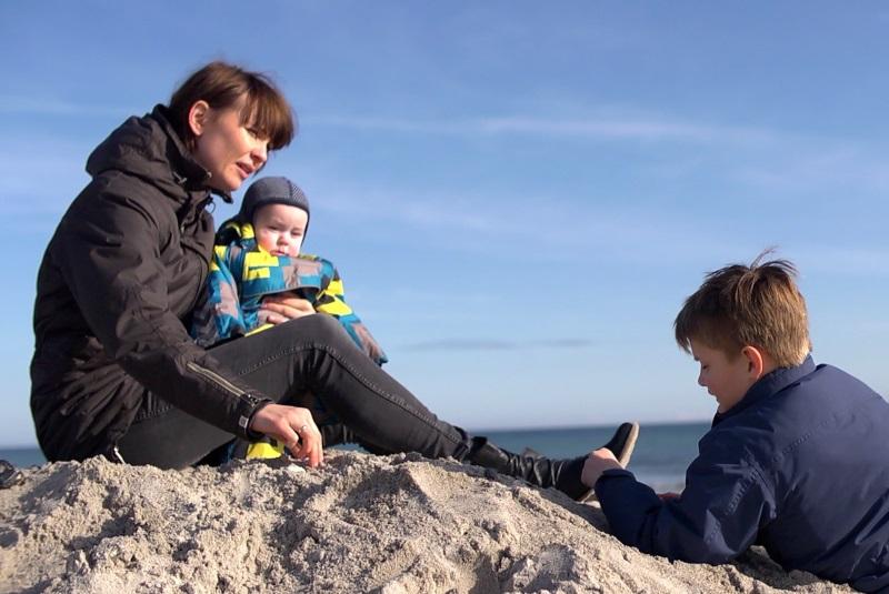 En familie sidder på en strand i Norddjurs