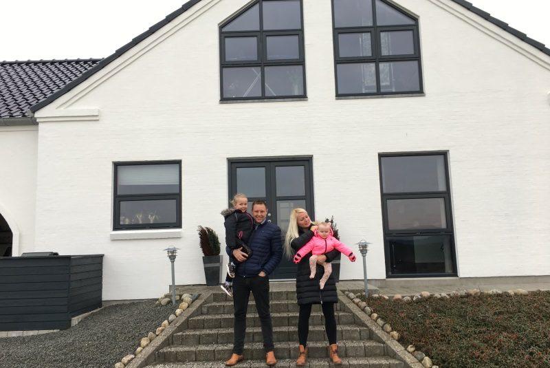 En far, mor og to børn står foran deres nybyggede hus i Auning, Norddjurs Kommune