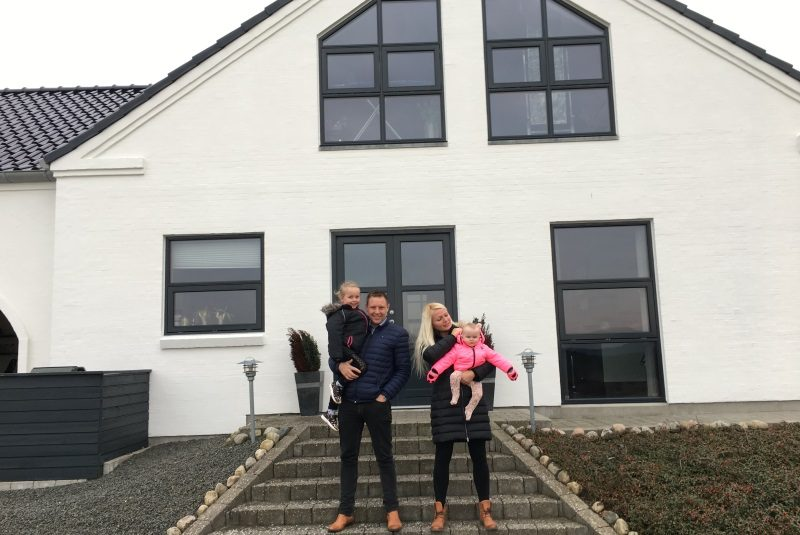 Familie står foran deres nybyggede hus i Auning