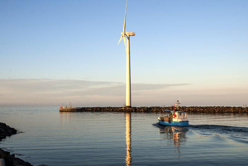 Havnemole med en vindmølle og et sejlende skib i sigte