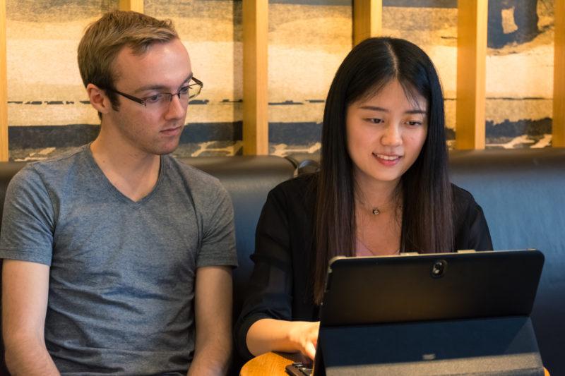 Ung mand og kvinde taler ved en bærbar computer.