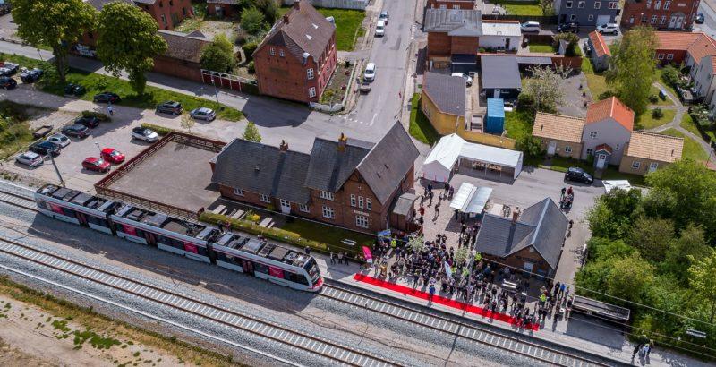 Trustrup Station med holdende letbanetog og menneskemylder